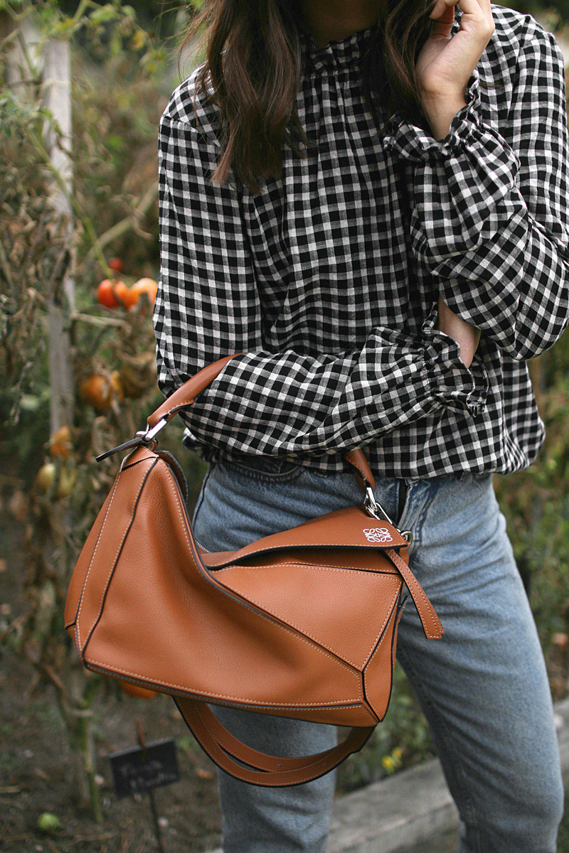 Nisi is wearing: Gingham pattern blouse, Gucci Princetown Slipper, Loewe Puzzle bag, mo jeans