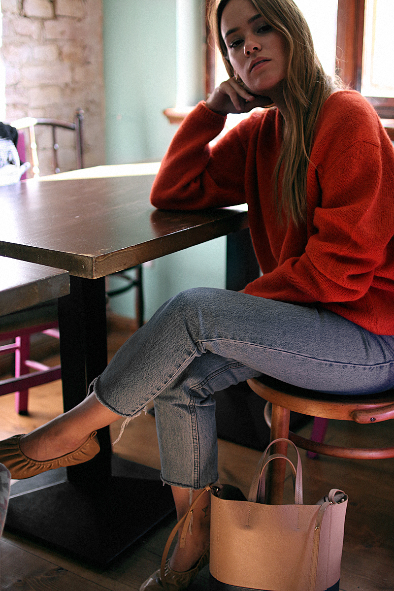 Desi is wearing: Céline Soft Ballerina Flats, Céline Small Cabas Tote, Mom jeans, red sweater