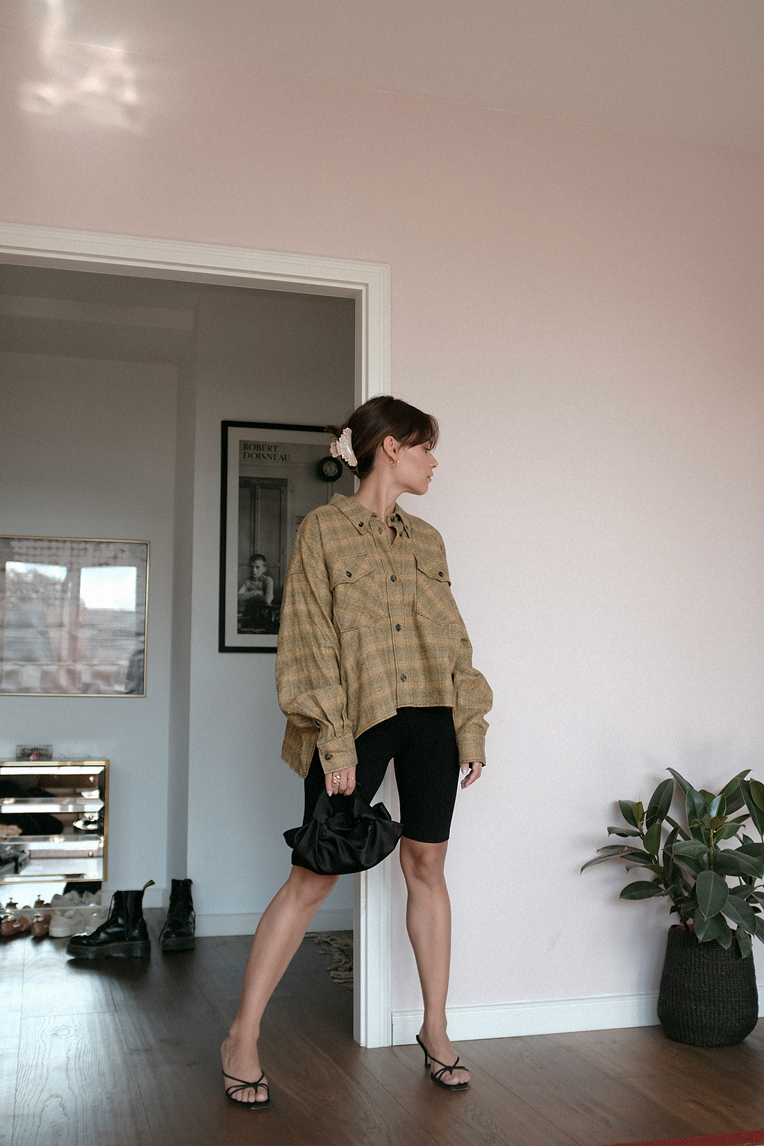 Nisi is wearing: Isabel Marant Etoile delora checked cotton shirt, cycling shorts, The Row Ascot bag, Alighieri jewelry, strappy sandals, crystal hair clip