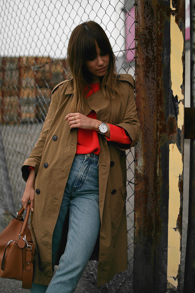 Nisi is wearing: Mango Trenchcoat, Red jumper, Gucci Princetown slipper, Denim mom jeans, Loewe Puzzle bag
