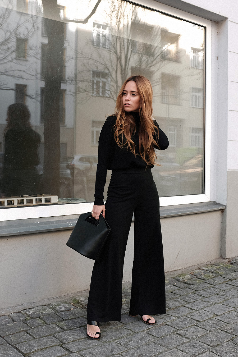 Outfit: All Black. Desi is wearing: Bucket bag, Wool turtleneck, toe mules, wide pants