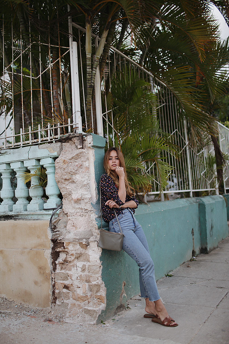 Desi is wearing: Hermès Oran Sandals, Céline Trio Bag, Silk blouse, Mom jeans