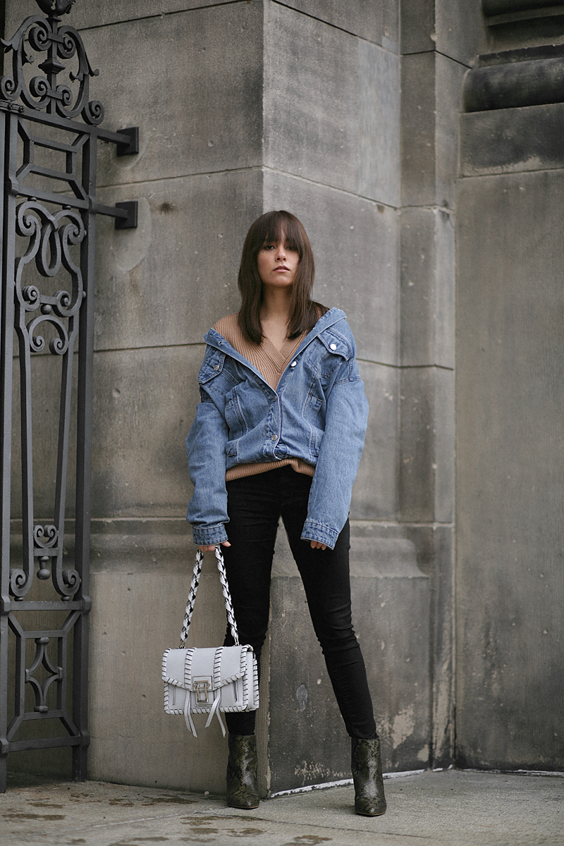 Nisi is wearing: Denim Jacket alla Balenciaga, Proenza Shoulder Hava bag, Python print boots, Cornelia Webb Earrings, Nude sweater, Black skinny jeans