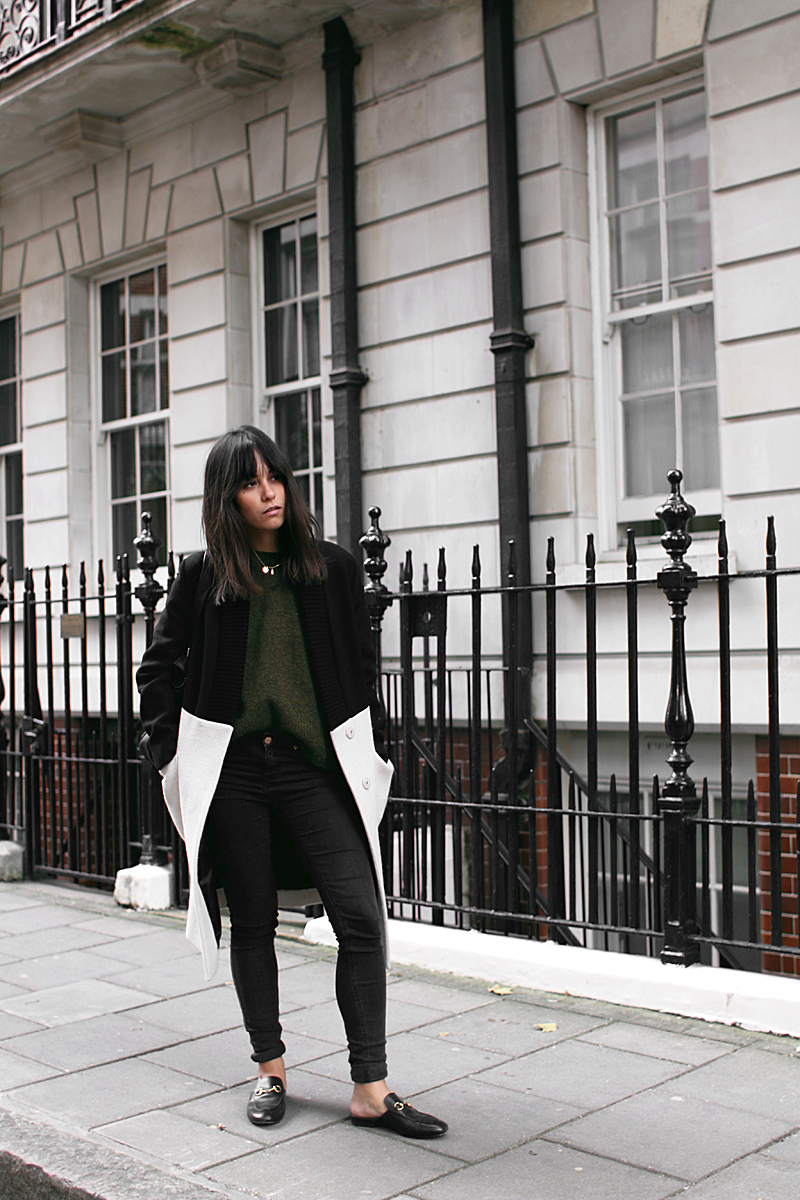 Nisi is wearing:  Céline Edge bag, Gucci Princetown slipper, Üterque two-tone coat,green sweater, skinny jeans