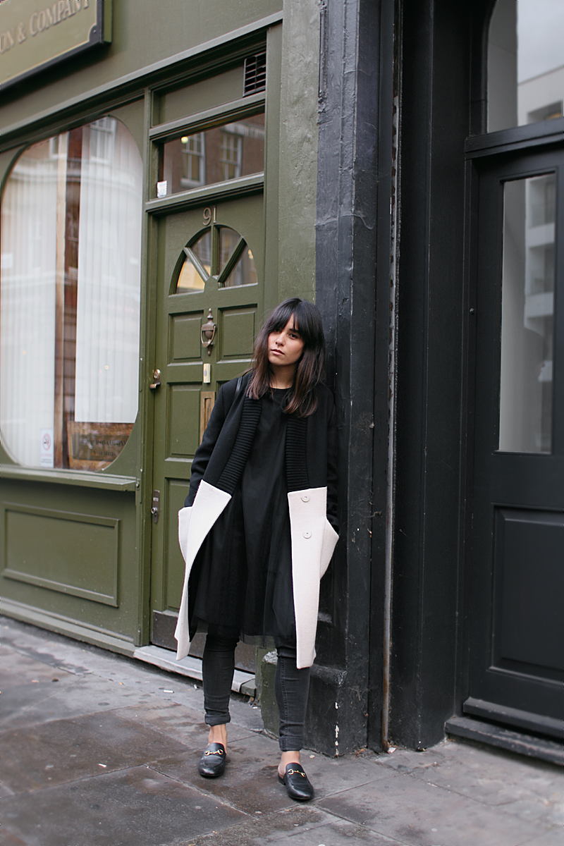 Nisi is wearing: Gucci Princetown slipper, Üterque two-tone coat, black mesh dress, skinny jeans