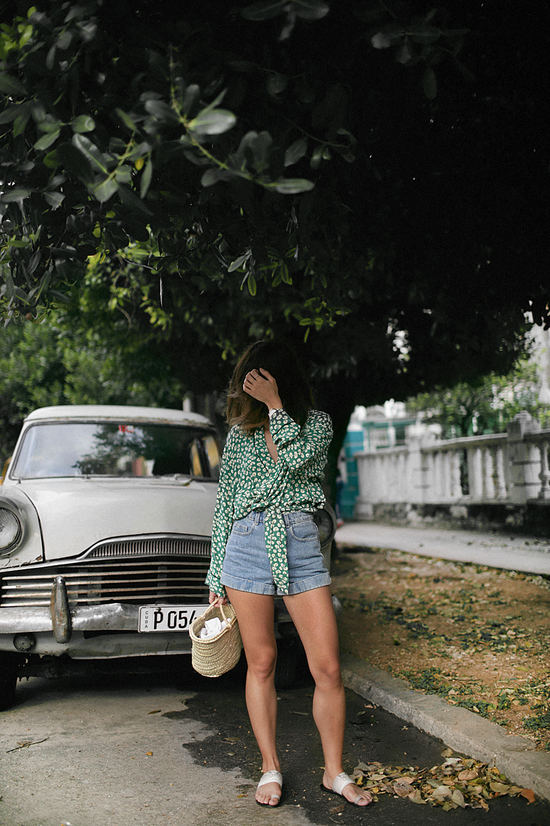 Nisi is wearing: Ganni Kimono, high-waisted denim shorts, straw bag, sandals, gold mesh watch