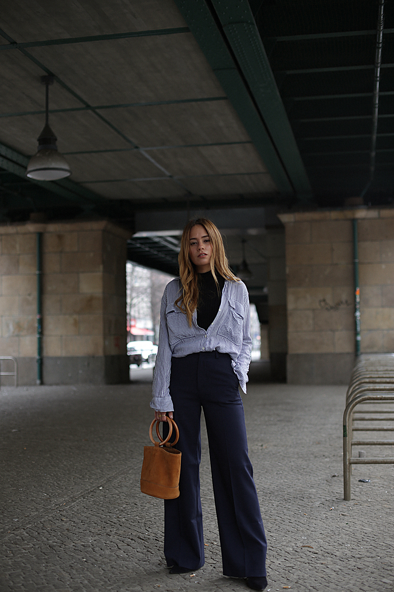 Layering. Desi is wearing: Striped button-down Shirt, turtleneck shirt, pants with wide legs, Saint Laurent pointy stilettos, Simon miller bonsai bucket bag, statement earrings