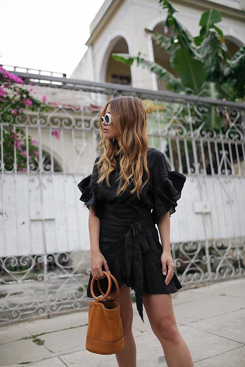 Desi is wearing: Isabel Marant Étoile Delicia dress, Hermès Oran sandals, Simon Miller Bonsai bag, Acne Studios Mustang sunglasses