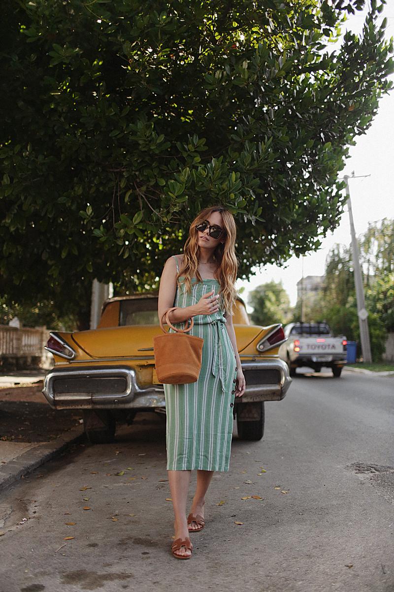 Desi is wearing: Hermès Oran sandals, Simon Biller Bucket Bag Bonsai, Green striped linen dress, Céline Tilda Sunglasses