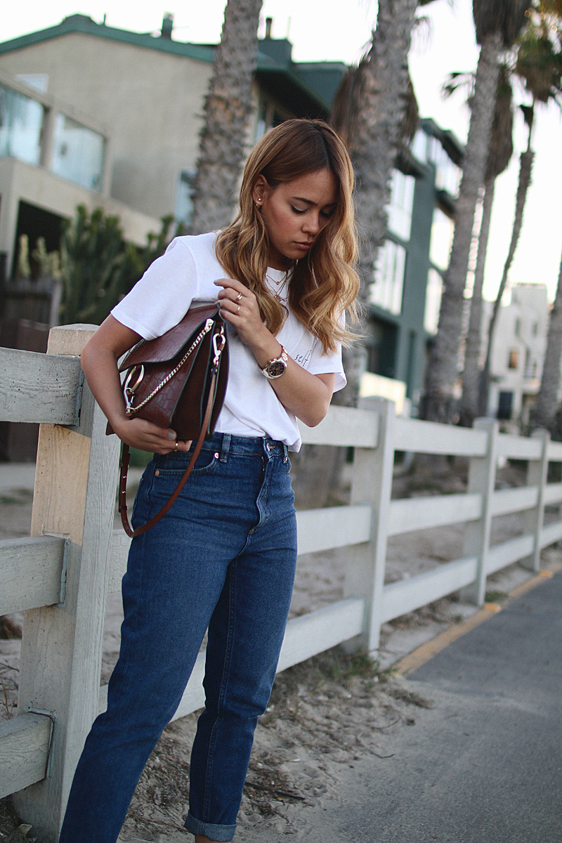 Outfit: Simplicity in Los Angeles. Desi is wearing TwoSongs shirt, Monki mom jeans, Gucci Princetwon slippers, Chloé Faye bag, Edited x Malaika Raiss popcorn necklace.