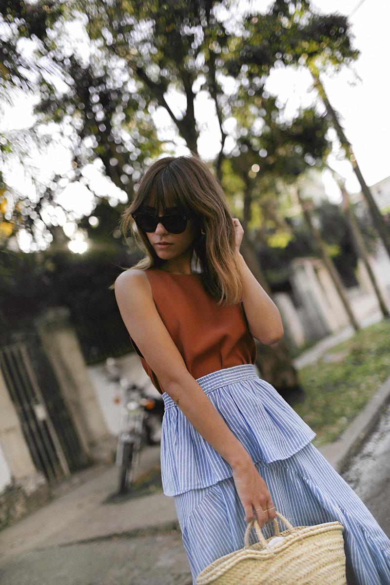 Nisi is wearing: Straw bag, striped skirt with volants, Céline Baby Audrey sunglasses, Nina Kastens Stella Earrings, Hermès Oran sandals