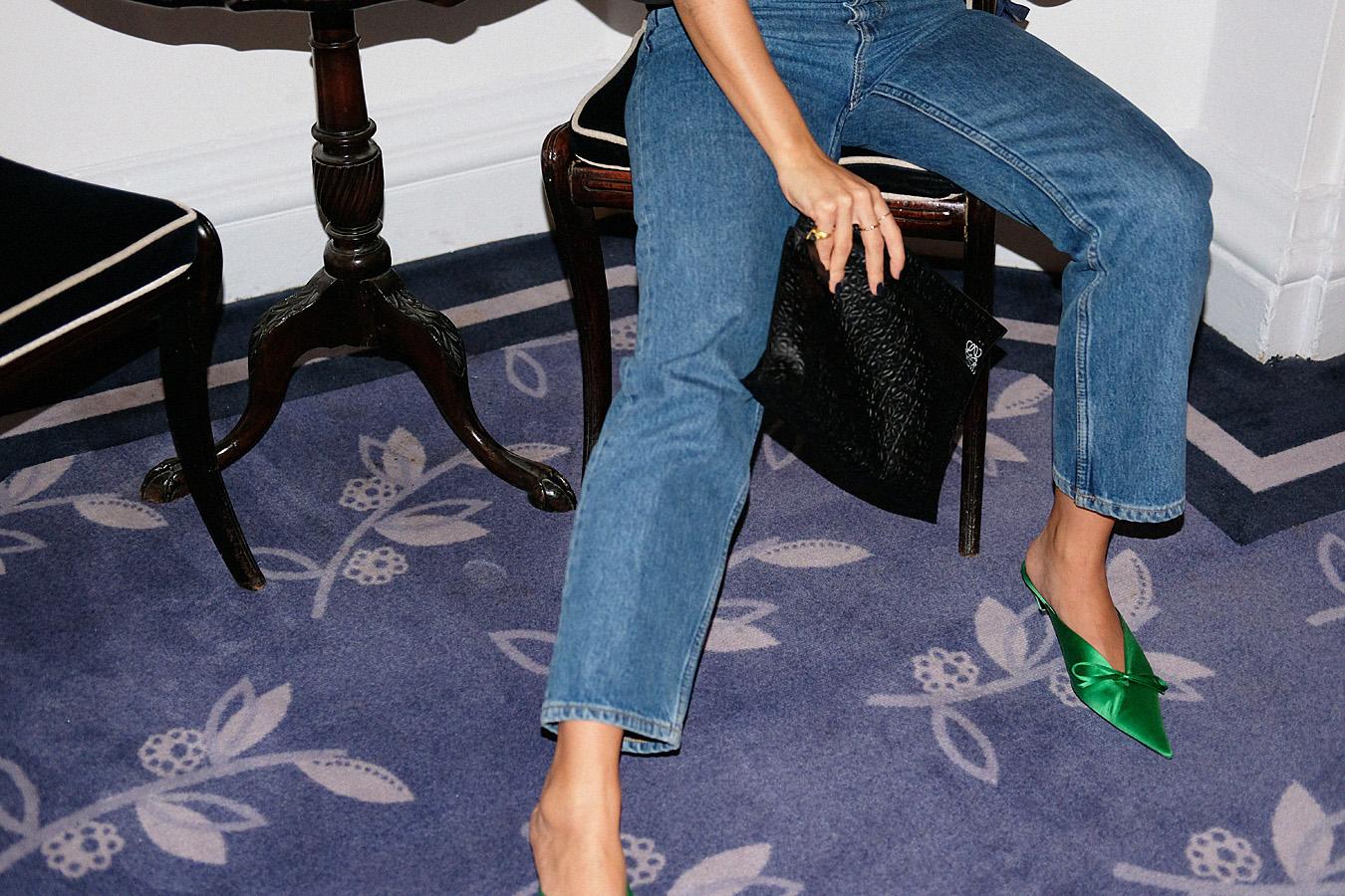Desi is wearing: Balenciaga Knife mules, Totême Azurro top, Loewe T Pouch, denim jeans, Rhinestones earrings