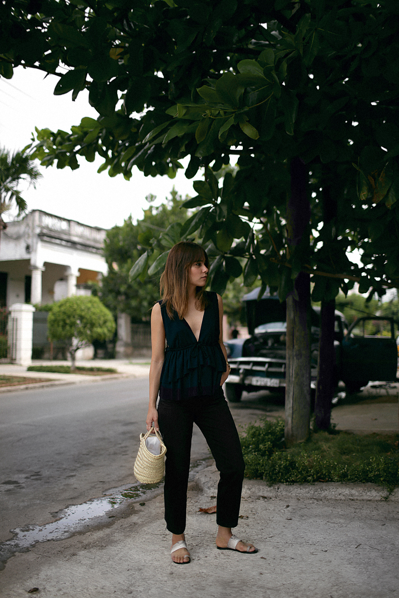 Nisi is wearing: See by Chloé top with ruffles, black denim mom jeans, ATP Atelier sandals, Straw bag, Rosefield gold mesh watch