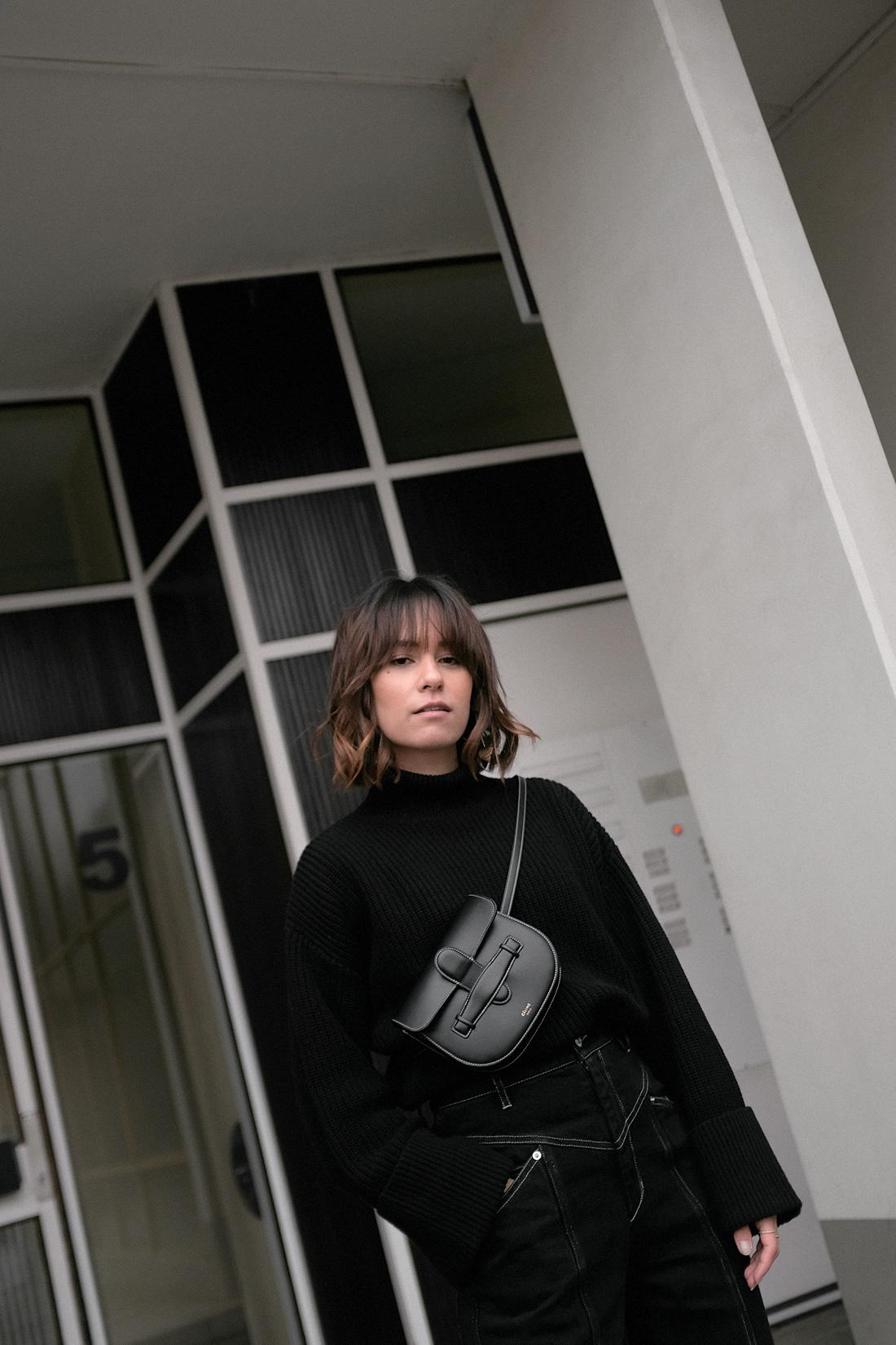 Nisi is wearing: Isabel Marant jeans, Céline Mini Symmetrical Bag, Céline Madame boots, Black turtleneck knit